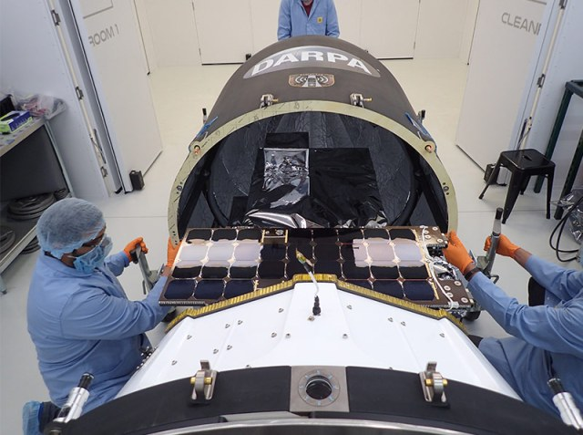 three workers in blue lab uniforms working on spacecraft