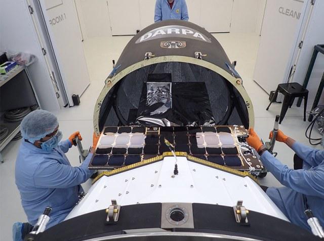 three workers in blue lab uniforms working on spacecraft