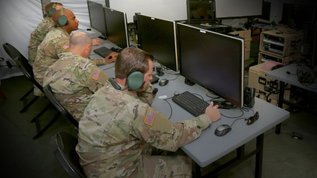 four men in military uniforms sitting at computer terminals