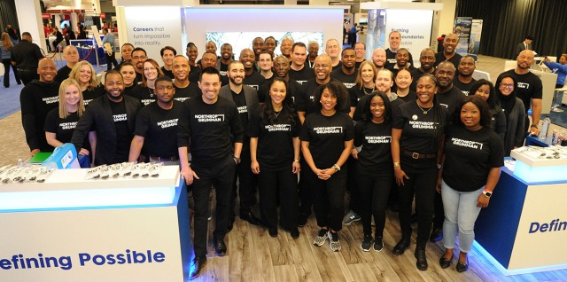 Northrop Grumman employees in black shirts pose at event booth