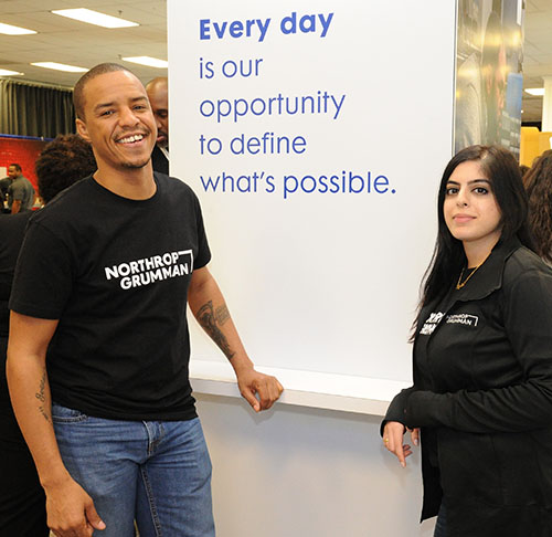 Man and woman in black Northrop Grumman shirts pose in front of banner