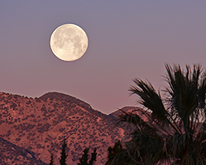 This full moon is about to set over the Huachuca Mountains to the west of Sierra Vista, Arizona just as the sun is rising over the Dragoon mountains to the east.