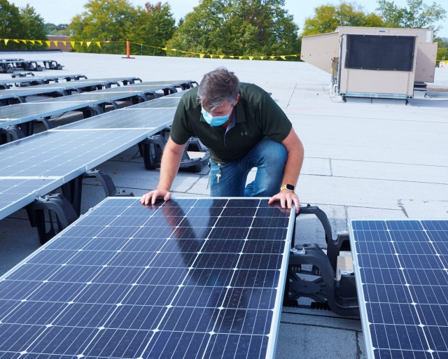 man on a roof working on solar panels