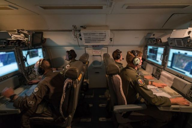 Air crewmen monitor data from computers on an airplane