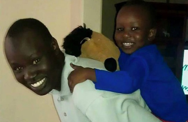 Black male smiling while carrying male child on his back