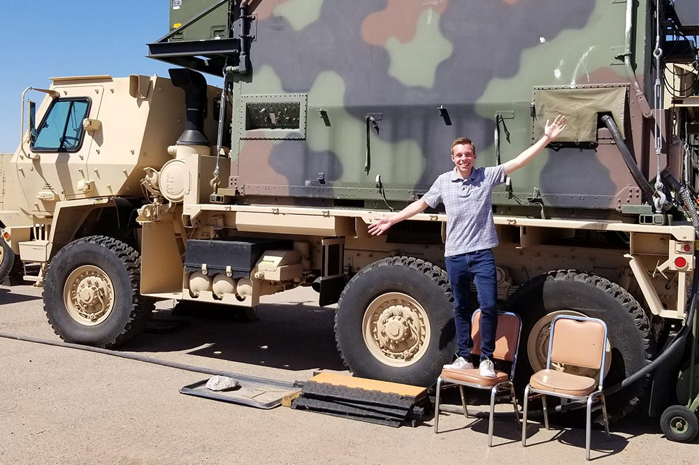 Young man standing in front of large camoflauged truck