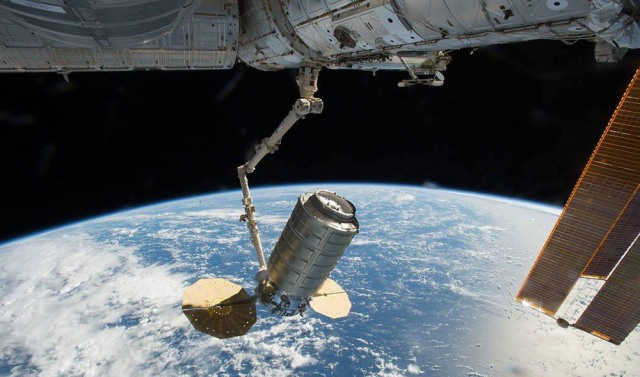Cygnus equipment floating in space with earth in background