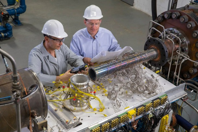 Two men in hard hats look at instruments on a table in a manufacturing setting.