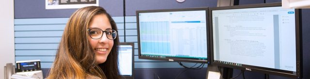 Woman wearing glasses sitting at desk with two monitors