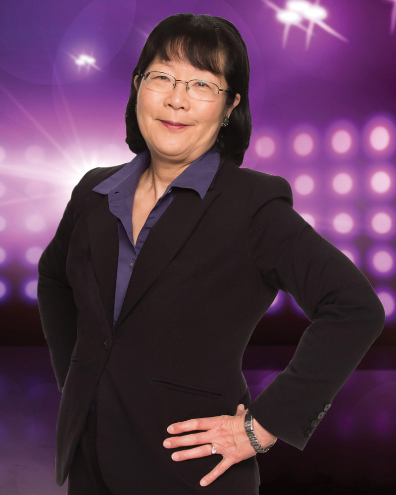 Asian American Female posing for photo against purple backdrop