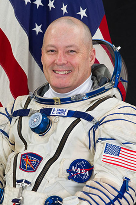Bald man wearing astronaut uniform in front of American Flag
