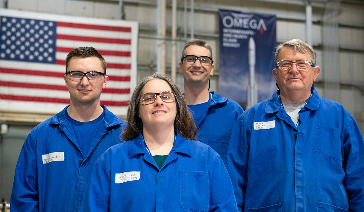 Three males and one female all standing in front of the American Flag and an OmegA banner