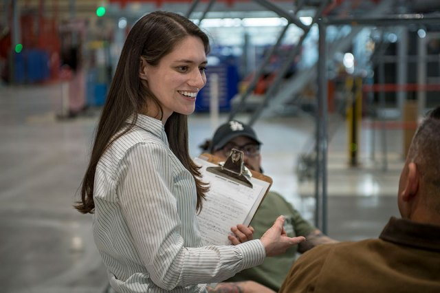 Young Woman holding clipboard and smilin in facility