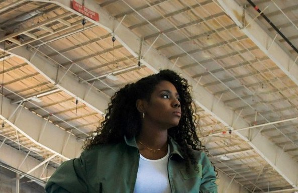 African American Female standing in Hangar with Large plane