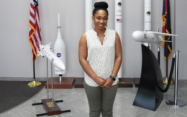 Young African American woman smiling and posing in front of model rockets