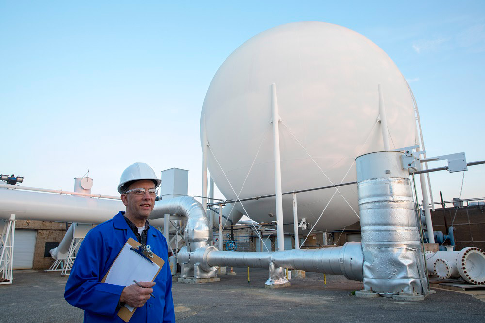Man in hard hat in front of Northrop Grumman Vacuum Sphere Ejector System