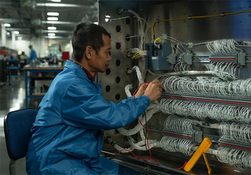 Technician works with many wires in an manufacturing setting.