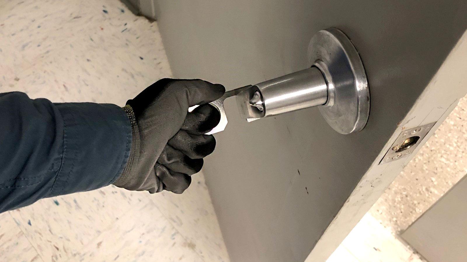 gloved hand turning door knob
