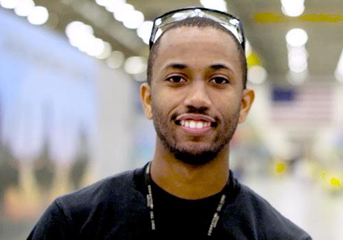 Black man smiles posing in hangar