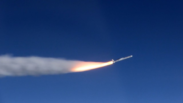A rocket blasting off in blue sky with a plume