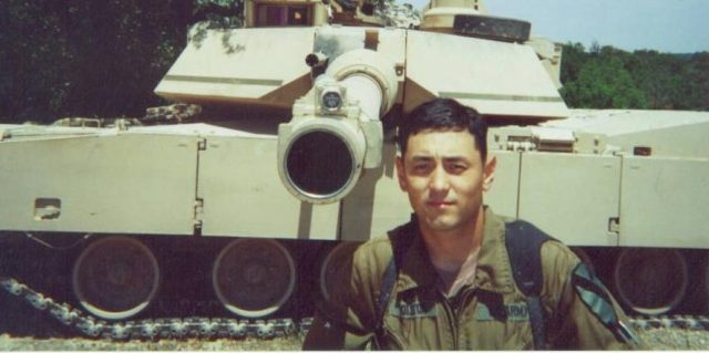 man standing in front of military tank