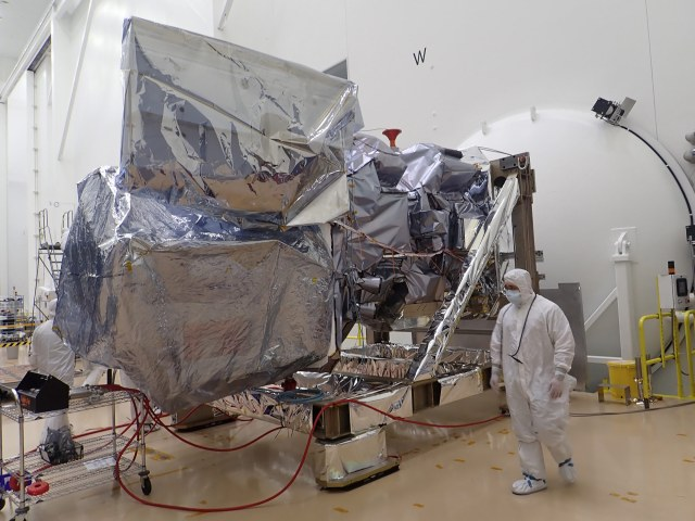 a person in a clean suit walks around a large machine covered in silver foil