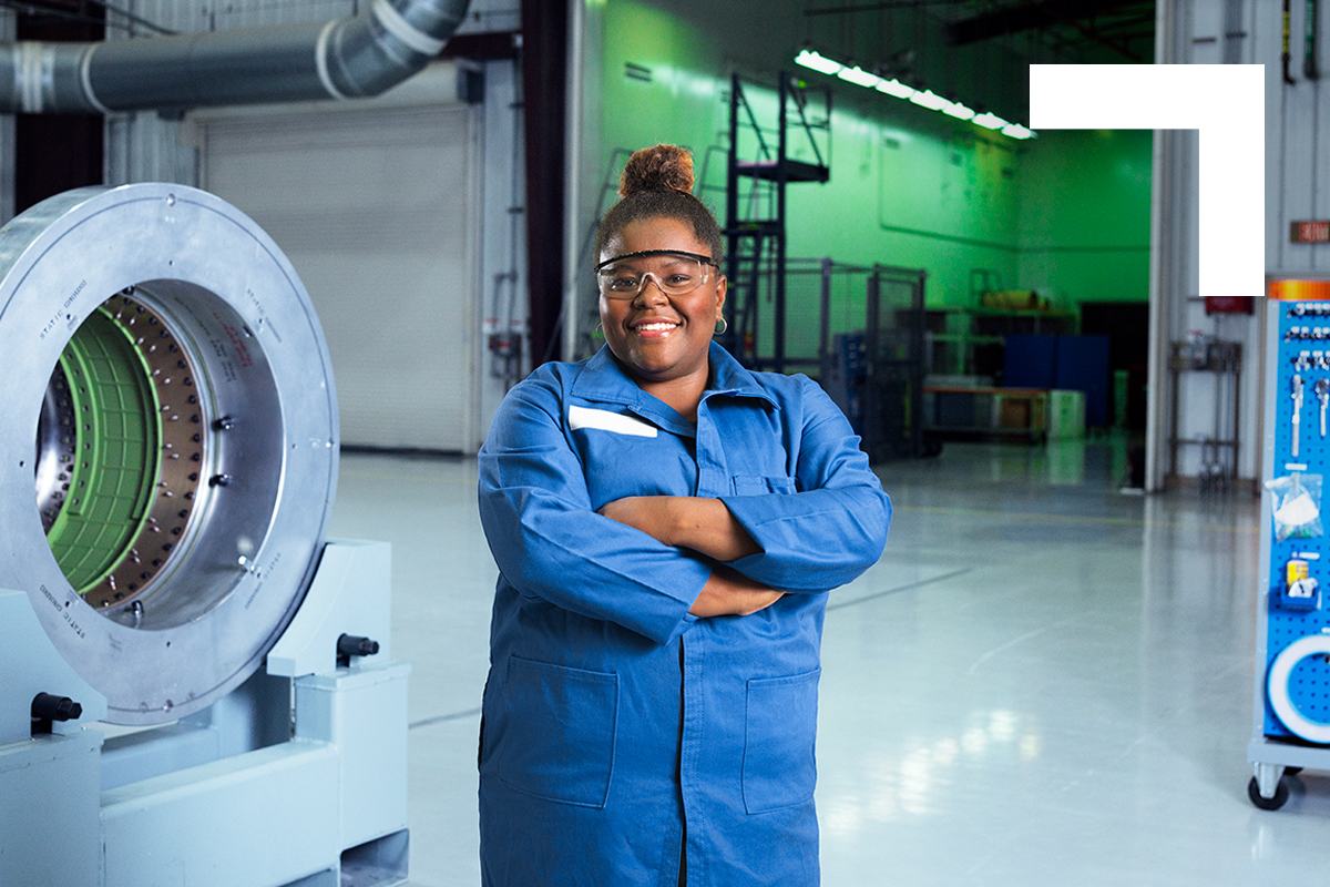 African American female wearing blue jumpsuit posing with arms crossed in front of production plant