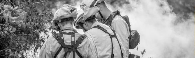 Black and white image of three firefighters gathered outside