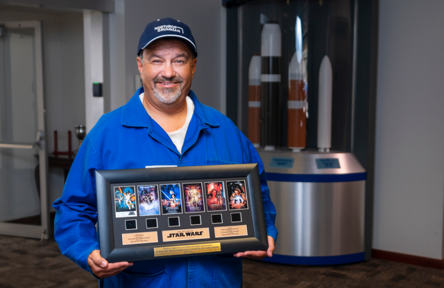 A Latino man in a blue work suit and cap holding a plaque