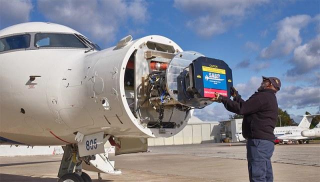 man installing radar in plane nose