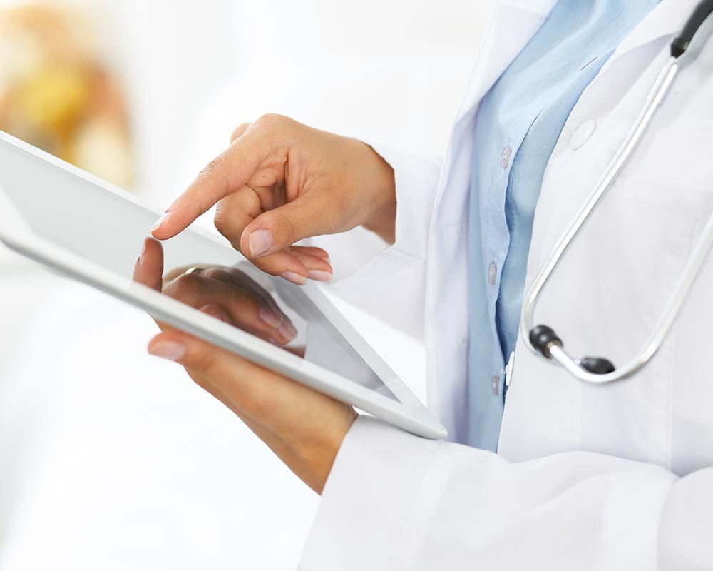 Close-up on a doctor's hands using a tablet