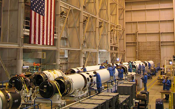 Workers in factory setting working on missile laying horizontal in the hanger. American flag hanging in the background