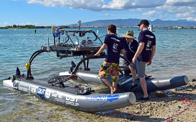three people working on solar boat on beach