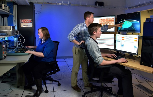 Two white males and a female in a blue lit room loooking at computer screens