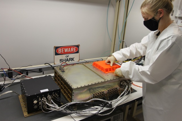 A white woman in a white lab coat test a hardware system