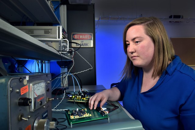 a white woman in a blue blouse works on a radio in a lab