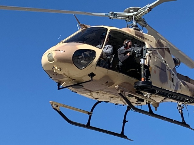 Man holding weapon in flying helicopter