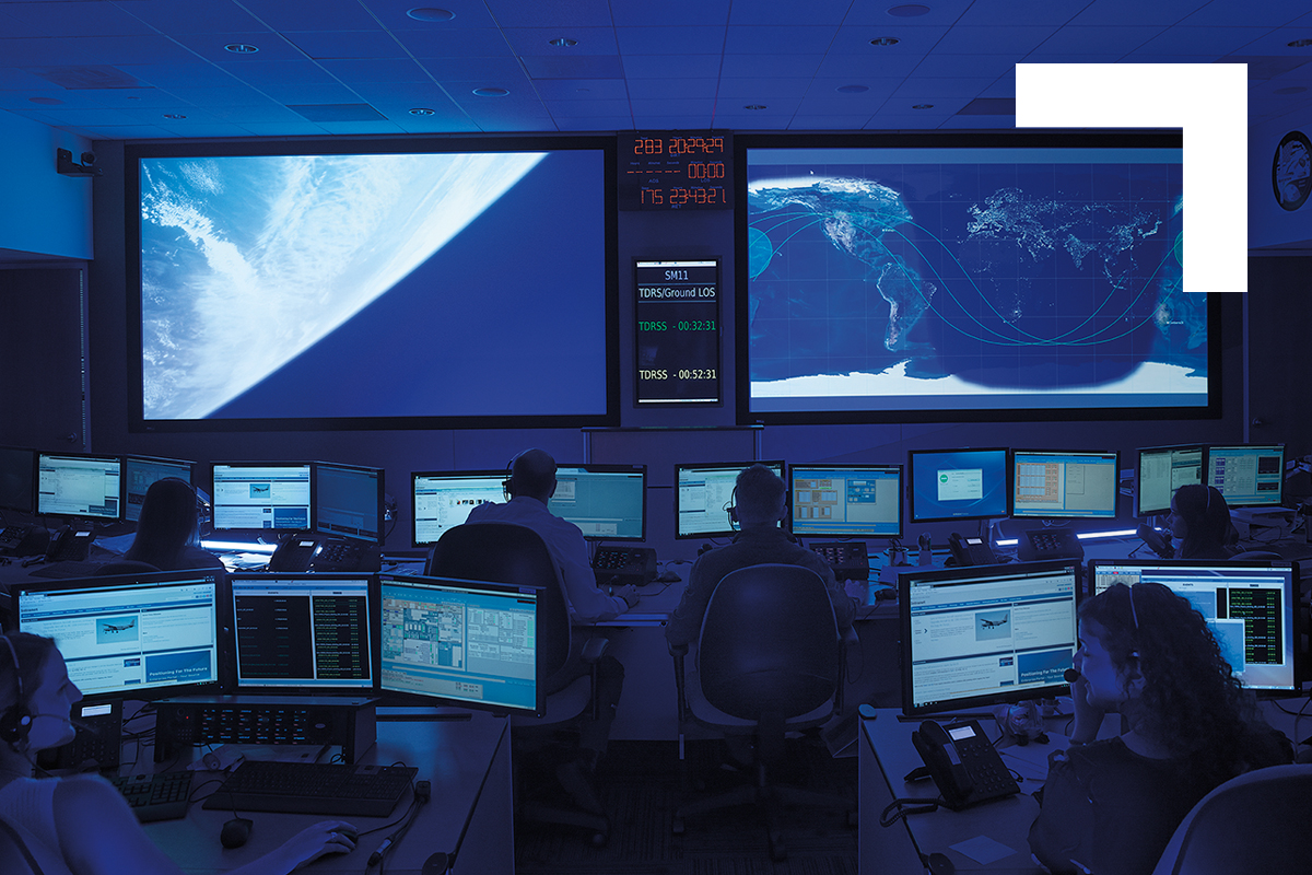 Two large projection screen monitors in data center with several workstations with dual monitors and various employees working