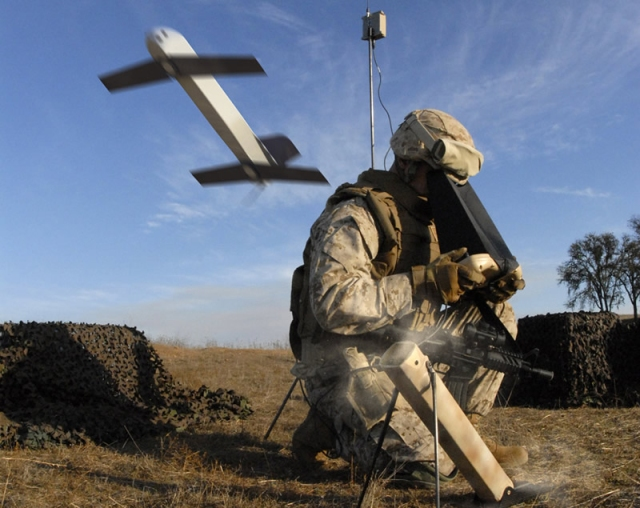 a soldier on the battlefield looks into a machine while an aircraft flies behind him