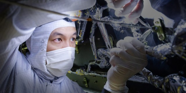 man in clean suit working on space ship telescope