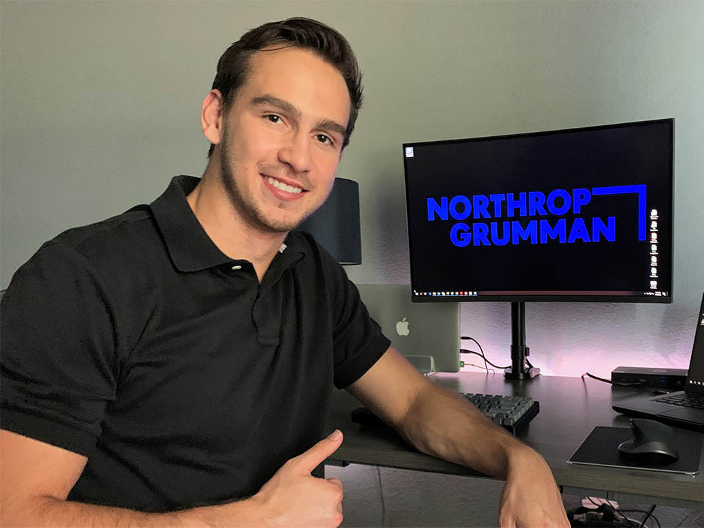 White male in front of computer screen with thumbs up