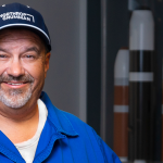 A Latino man in a blue work suit and hat