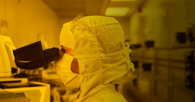 woman in clean room wearing full bunny suit looking through microscope