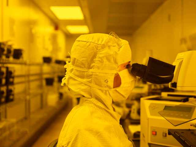 Woman wearing PPE in a clean room with a yellow tint, looking into microscope.