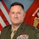US Marine headshot with american flag in background