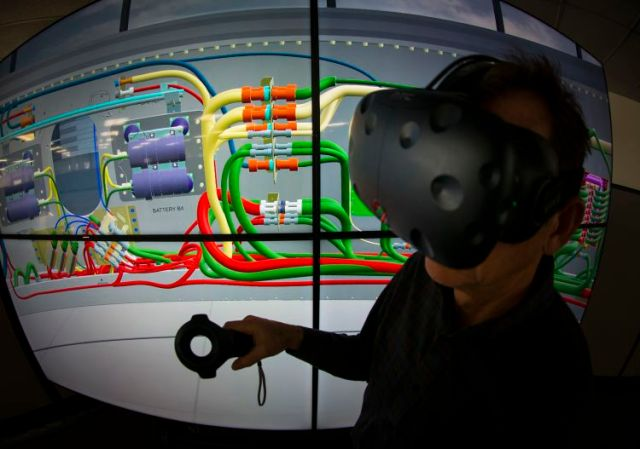 a man wears a VR headset in front of a computerized image