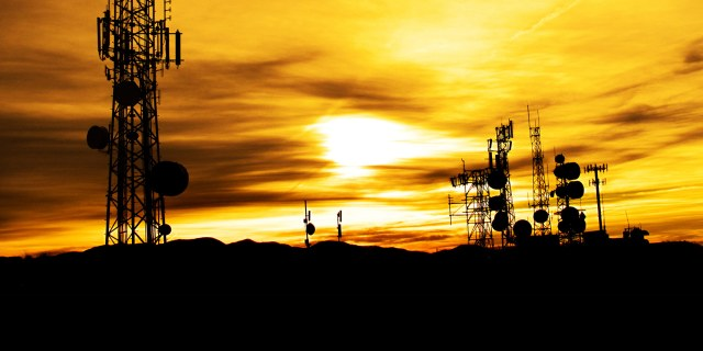 silhouette of transmission towers at sunset