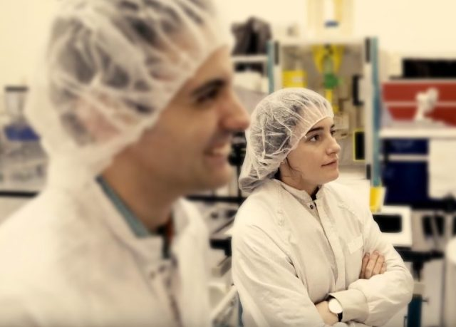 Male and female scientists in lab clothing.