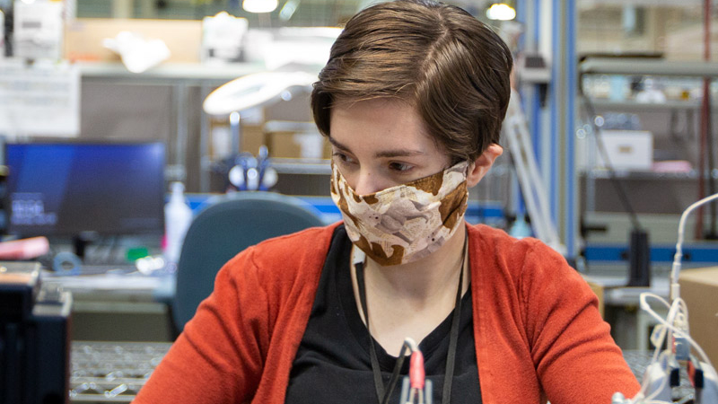 White female wearing mask working in a manufacturing environment.