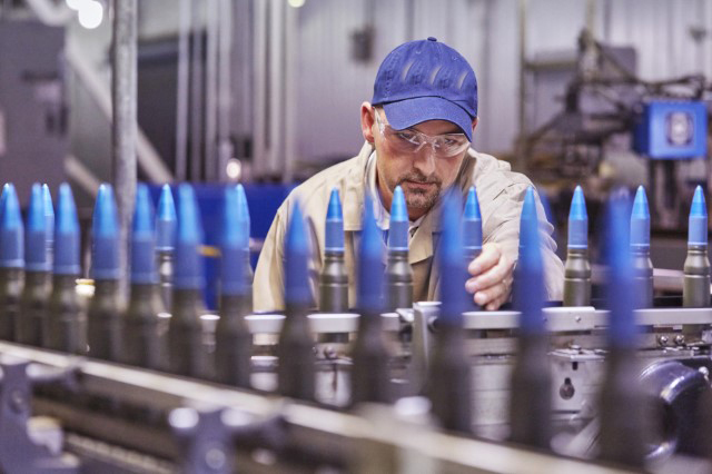This is a man with a blue hat at an armament facility.